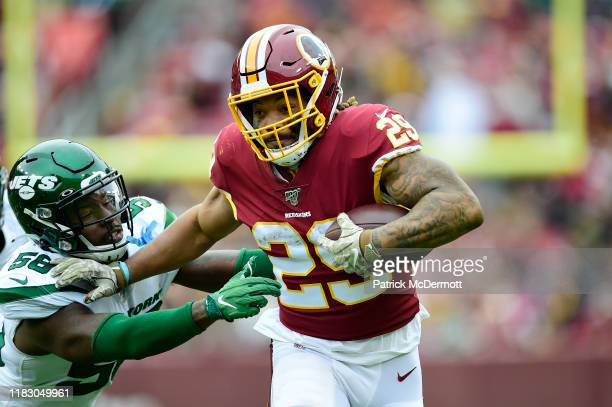 Derrius Guice of the Washington Redskins runs with the ball against James Burgess of the New York Jets in the first half at FedExField on November...