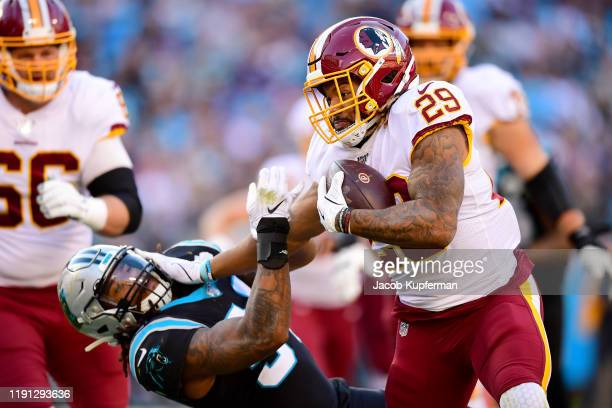 Derrius Guice of the Washington Redskins stiff arms Shaq Thompson of the Carolina Panthers during the fourth quarter during their game at Bank of...