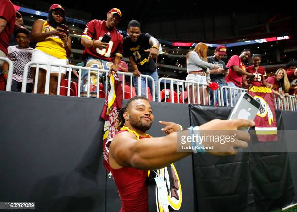 Derrius Guice of the Washington Redskins takes selfies with fans at the conclusion of an NFL preseason game against the Atlanta Falcons at...