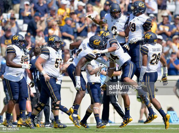 Derron Brown of the California Golden Bears celebrates sith teammates after intercepting a pass against the North Carolina Tar Heels during their...