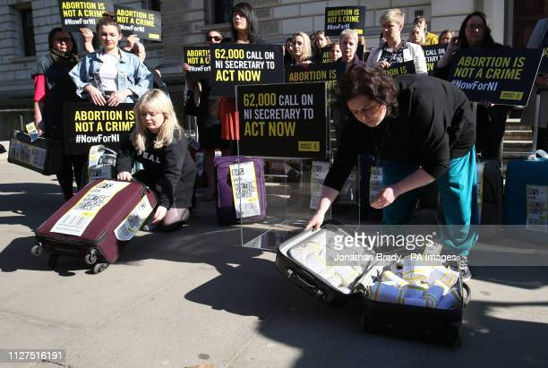 Derry Girls cast members Siobhan McSweeney and Nicola Coughlan open suitcases outside the Treasury in Westminster to reveal the signatures on the...