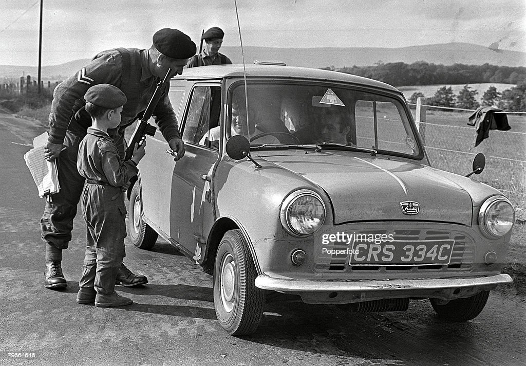 Derry, Northern Ireland, 20th August 1970, 5 year old Malcolm Burns of Londonderry holding a gun as he assists a soldier of the Ulster Defence Regiment to check vehicles entering Derry from across the Northern Ireland border