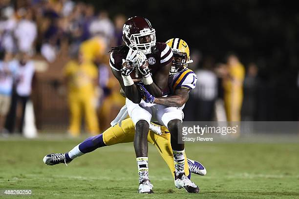 De'Runnya Wilson of the Mississippi State Bulldogs is brought down by Dwayne Thomas of the LSU Tigers during a game at Davis Wade Stadium on...