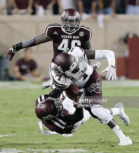 De'Runnya Wilson of the Mississippi State Bulldogs is tackled by De'Vante Harris of the Texas AM Aggies in the second quarter on October 3 2015 at...