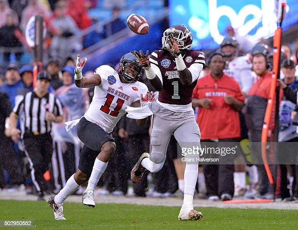 De'Runnya Wilson of the Mississippi State Bulldogs makes a catch against Juston Burris of the North Carolina State Wolfpack during the Belk Bowl at...