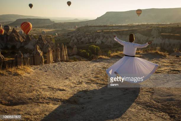 dervish doing the retual in love valley of cappadocia with balloons in background at sunrise. - sufism stock photos and pictures