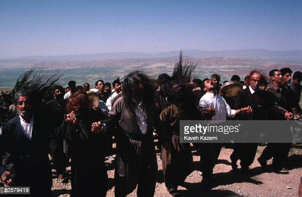 Dervish pilgrims hold hands and shake their hair in an act of remembrance to a tambourine accompaniment 17th June 1997 They are climbing the hill to...