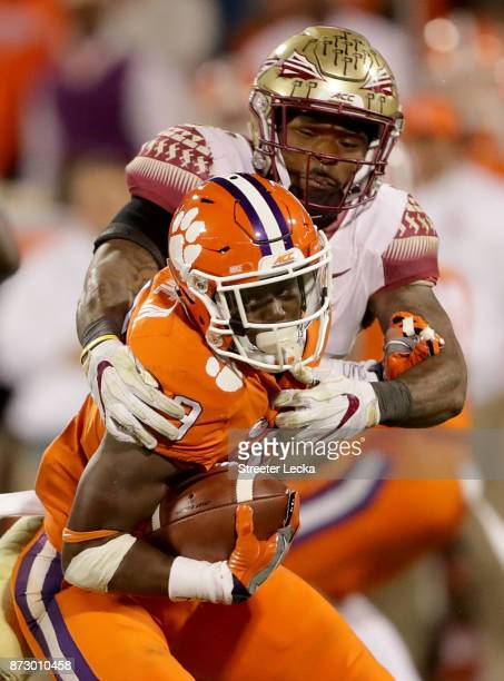 Derwin James of the Florida State Seminoles tries to stop Travis Etienne of the Clemson Tigers during their game at Memorial Stadium on November 11...