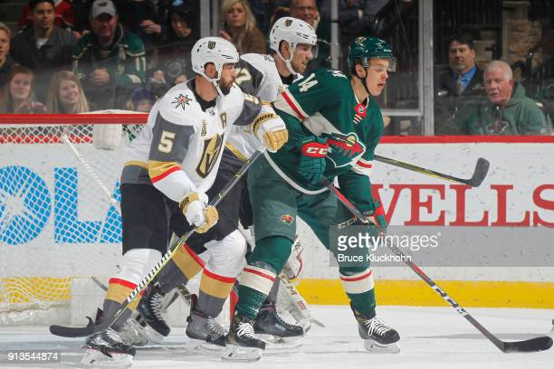 Deryk Engelland and Shea Theodore of the Vegas Golden Knights defend against Joel Eriksson Ek of the Minnesota Wild during the game at the Xcel...