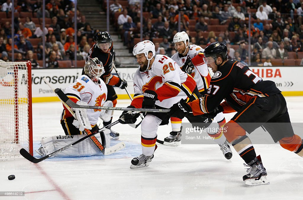 Deryk Engelland #29 of the Calgary Flames and Nick Ritchie #37 of the Anaheim Ducks battle for a loose puck as Karri Ramo #31 of the Calgary Flames tends goal during the third period of a game at Honda Center on November 24, 2015 in Anaheim, California.