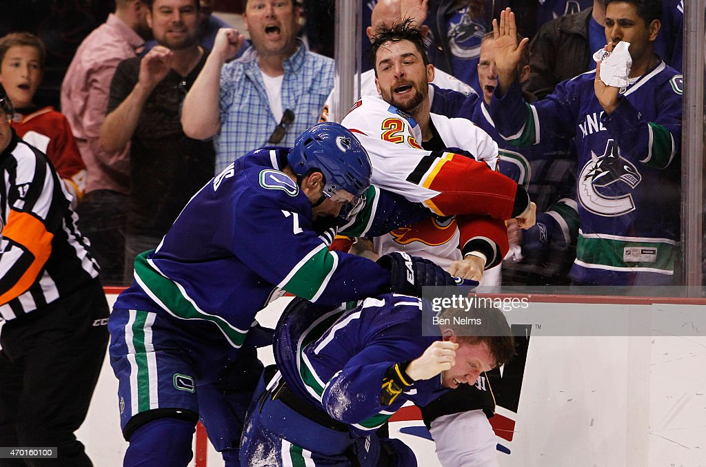 Deryk Engelland #29 of the Calgary Flames fights with Dan Hamhuis #2 and Derek Dorsett #51 of the Vancouver Canucks during Game Two of the Western Conference Quarterfinals during the 2015 NHL Stanley Cup Playoffs at Rogers Arena on April 17, 2015 in Vancouver, B.C, Canada.