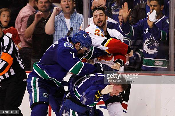 Deryk Engelland of the Calgary Flames fights with Dan Hamhuis and Derek Dorsett of the Vancouver Canucks during Game Two of the Western Conference...