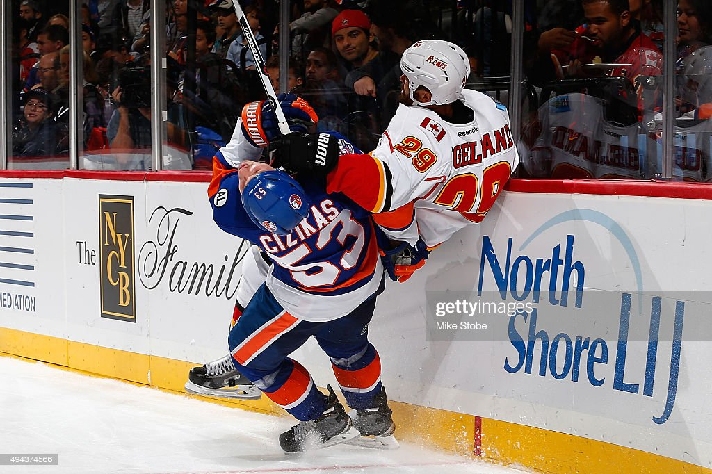 Deryk Engelland #29 of the Calgary Flames gets tripped up with Casey Cizikas #53 of the New York Islanders during the game at the Barclays Center on October 26, 2015 in Brooklyn borough of New York City.