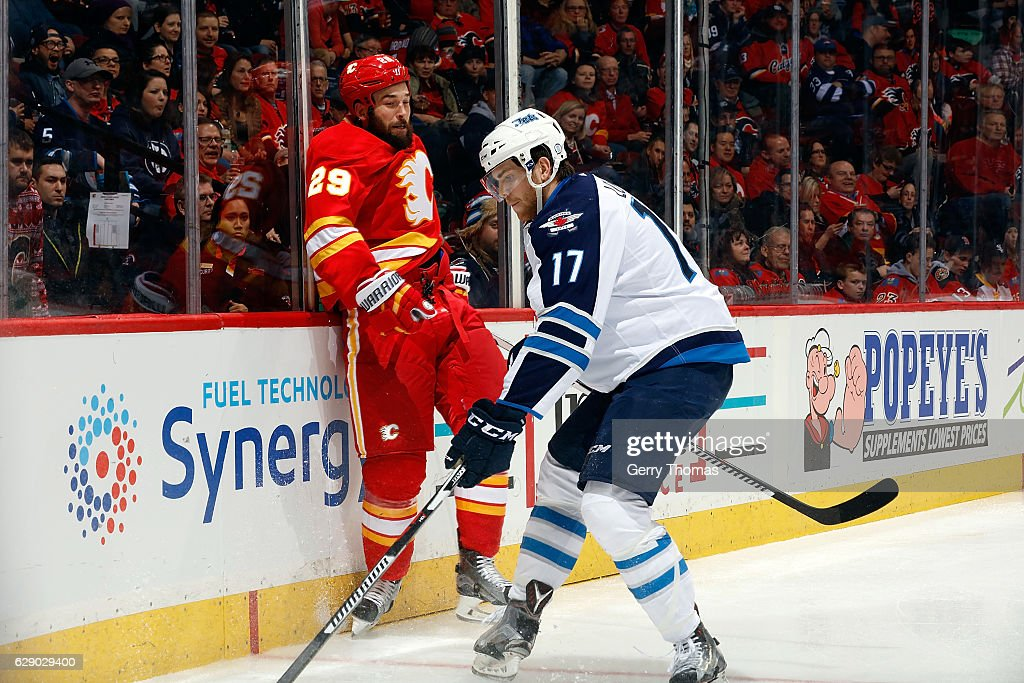 Deryk Engelland #29 of the Calgary Flames skates against Adam Lowry #17 of the Winnipeg Jets during an NHL game on December 10, 2016 at the Scotiabank Saddledome in Calgary, Alberta, Canada.