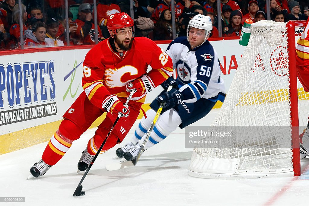 Deryk Engelland #29 of the Calgary Flames skates against Marko Dano #56 of the Winnipeg Jets during an NHL game on December 10, 2016 at the Scotiabank Saddledome in Calgary, Alberta, Canada.
