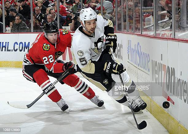 Deryk Engelland of the Pittsbugh Penguins chases after the puck as Troy Brouwer of the Chicago Blackhawks follows behind on February 20 2011 at the...