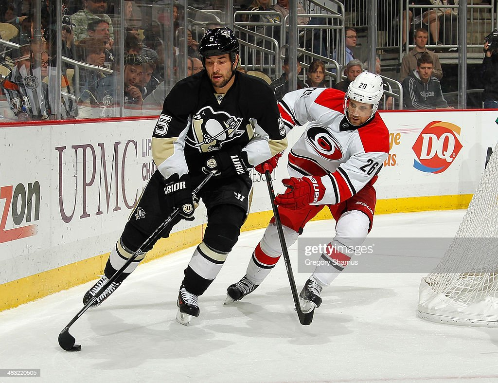 Deryk Engelland #5 of the Pittsburgh Penguins moves the puck in front of John-Michael Liles #26 of the Carolina Hurricanes on April 1, 2014 at Consol Energy Center in Pittsburgh, Pennsylvania.