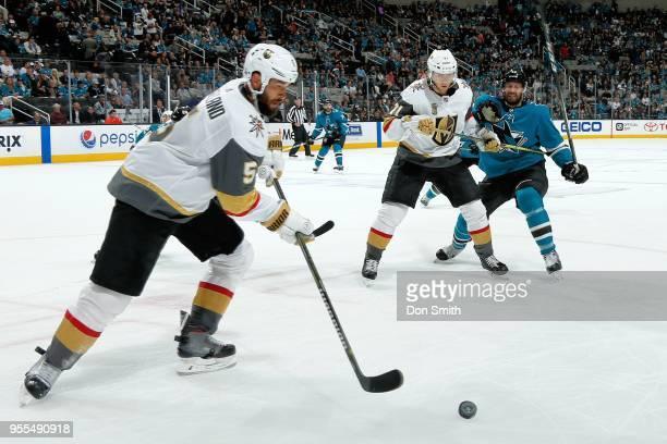 Deryk Engelland of the Vegas Golden Knights handles the puck as William Karlsson of the Vegas Golden Knights defends Eric Fehr of the San Jose Sharks...