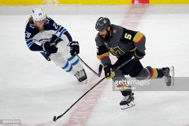 Deryk Engelland of the Vegas Golden Knights is defended by Patrik Laine of the Winnipeg Jets during the first period in Game Three of the Western...
