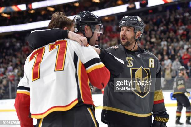 Deryk Engelland of the Vegas Golden Knights talks with an official and Mark Jankowski of the Calgary Flames during the game at TMobile Arena on...