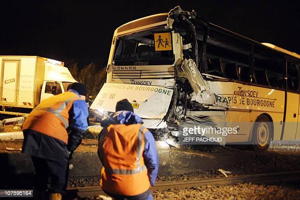Des agents communaux s'affairent autour d'un car scolaire accidenté après une collision avec un TER à un passage à niveau le 14 décembre 2010 à...