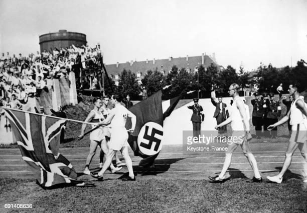 Des athlètes britanniques et allemands présentent leurs drapeaux lors d'une rencontre sportive au stade circa 1930 à Munich Allemagne