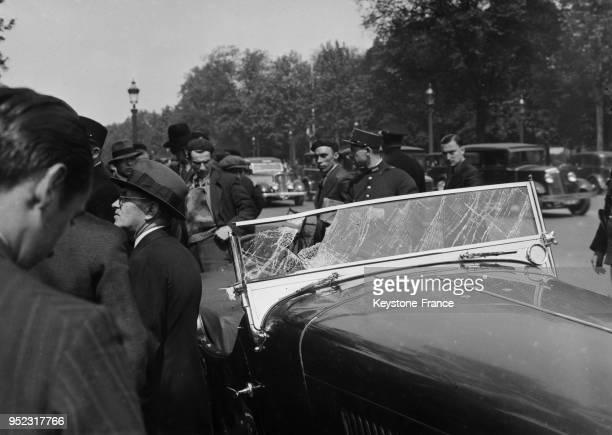 Des badauds et policiers entourent une voiture accidentée à Paris France en 1935