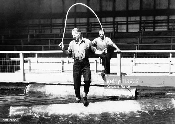 Des bûcherons font une démonstration de 'logrolling' saut à la corde sur des tuyaux à l'exposition universelle de Chicago aux EtatsUnis le 7 juin 1933