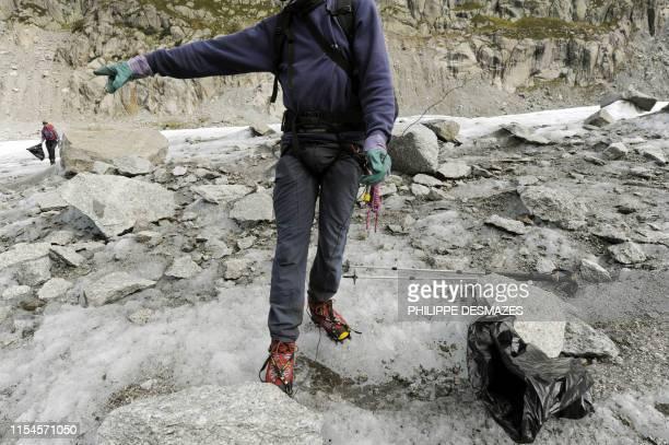 Des bénévoles ramassent des détritus le 1er octobre 2010 lors de l'opération de nettoyage de la Mer de Glace dans le Massif du MontBlanc près de...