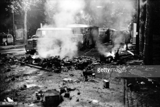 Des cars de CRS stationnent au milieu des débris fumant dans une rue dépavée du Quartier latin à la suite d'une nuit d'émeutes le 23 mai 1968 La...
