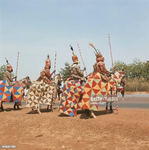 Des cavaliers djerma défilent décorés de riches étoffes et armés de heaume et lance au Niger vers 1960-1970. Des cavaliers djerma défilent décorés de...