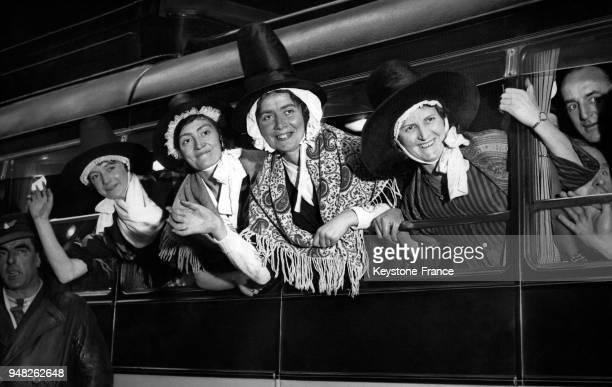 Des choristes de l'Ystelfera choeur gallois se penchent à la vitre d'un autobus lors de leur visite de la ville le 2 décembre 1933 à Londres...