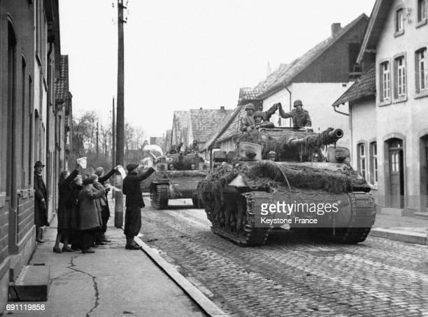 Des civils allemands agitent des drapeaux blancs devant le passage des chars de l'armée américaine le 9 avril 1945 à Lemgo Allemagne