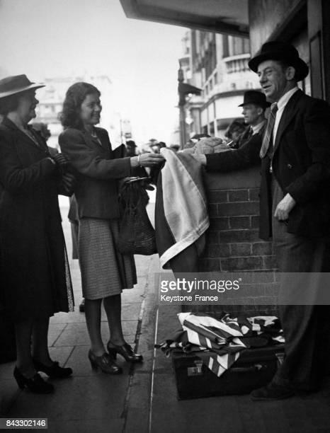 Des clientes achètent l'Union Jack à un vendeur de rue en vue de la parade de la Victoire en 1946 à Londres RoyaumeUni