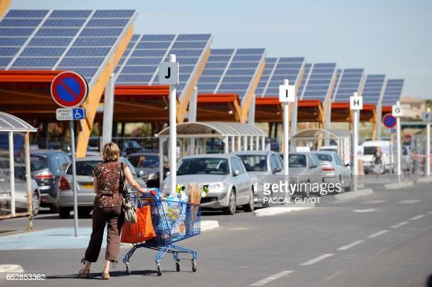 Des clients du centre commercial ELeclerc de SaintAunes passent le 12 juin 2008 sur le parking du supermarché équipé de 12 rangées d'ombrières de 85...