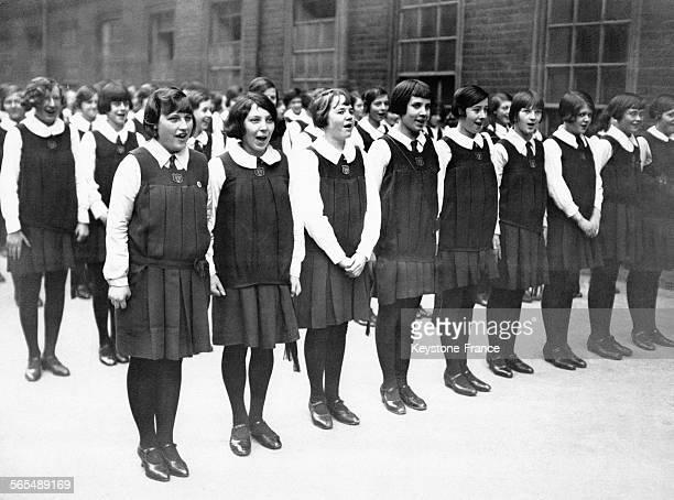 Des écolières britanniques en uniforme chantent pour fêter l'inauguration d'une nouvelle école le 6 février 1930 à Fulhma, Royaume-Uni.