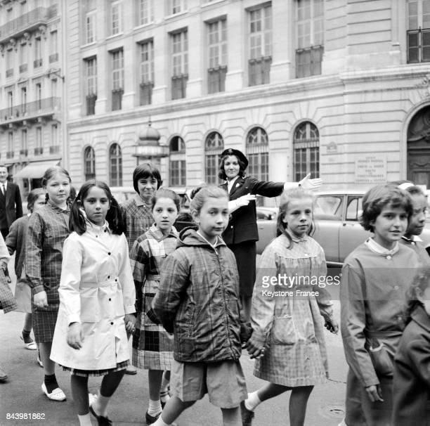 Des écolières traversent sur le passage clouté sous la protection d'une femme agent le jour de la rentrée des classes à Paris en France le 18...