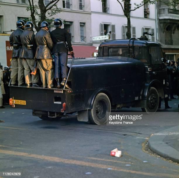 Des CRS debout sur un blindé circulant dans le quartier latin, à Paris, France, en mai 1968.