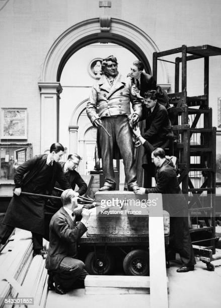 Des employés de la Royal Academy installent une statue imposante du peintre JMW Turner par le sculpteur William McMillan dans le musée en vue d'une...