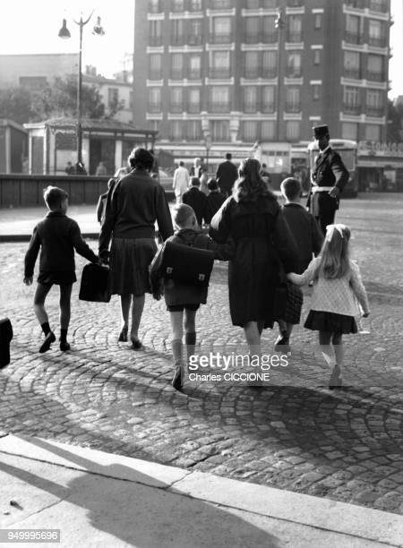 Des enfants accompagnes de leurs meres allant a l'ecole traversent la rue devant un agent de police circa 1960 a Paris France