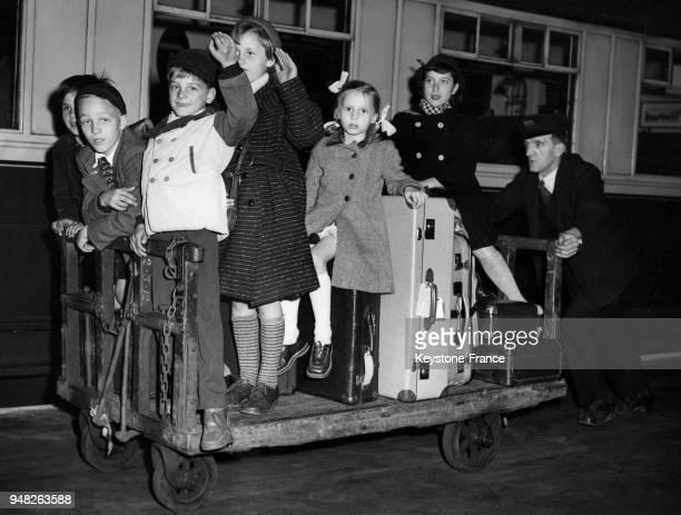 Des enfants allemands des camps de réfugiés de Hambourg sont poussés sur un chariot à bagages par un chef de gare pour les amuser à la gare de...