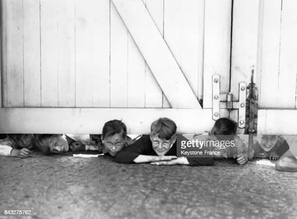 Des enfants espiègles laissent apparaître leur tête sous un portail en bois le 30 mai 1937 en Allemagne