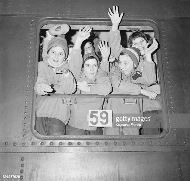 Des enfants partant en colonies de vacances au ski disent aurevoir de la fenêtre d'un train à la Gare de Lyon à Paris France le 20 décembre 1961