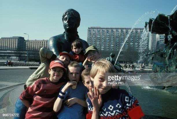 Des enfants posent à côté d'une fontaine à BerlinEst Allemagne le 7 mai 1985