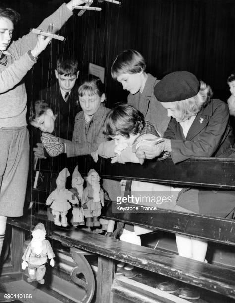 Des enfants regardent le spectacle de marionnettes 'Blanche Neige et les Sept Nains' organisé par des écoliers qui ont également fabriqué les...