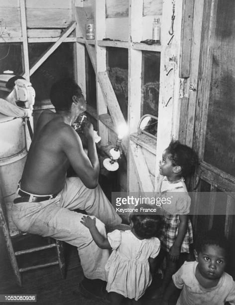 Des enfants regardent leur père se raser dans une maison du quartier pauvre de Miami, Floride, Etats-Unis, le 5 octobre 1967.