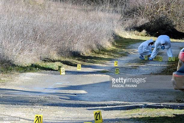 Des experts de la brigade scientifique examinent des traces sur un chemin de la commune de Bouloc le 15 février 2011 où des effets personnels de...