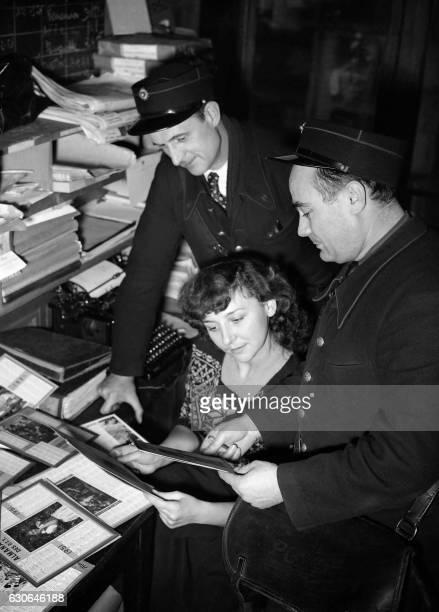 Des facteurs font leur tournée le 05 décembre 1950 pour proposer le calendrier des postes 1951 / AFP /