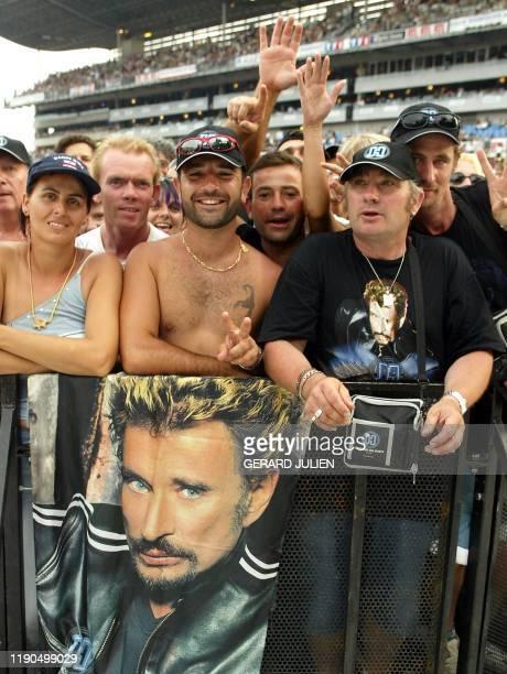 des fans du chanteur français Johnny Hallyday qui a récemment fêté ses 60 ans attendent le début du concert le 25 juin 2003 au stade Vélodrome de...