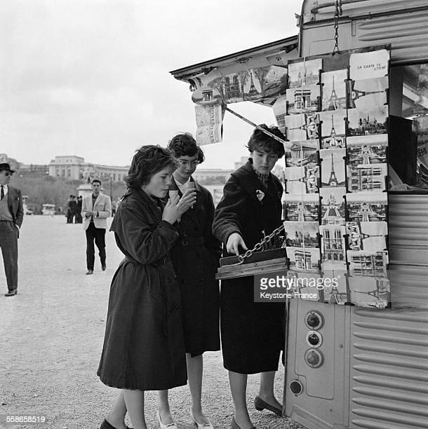 Des femmes choisissent des cartes postales pendant les vacances de Pâques près de la Tour Eiffel et du Palais de Chaillot le 18 avril 1960 à Paris...